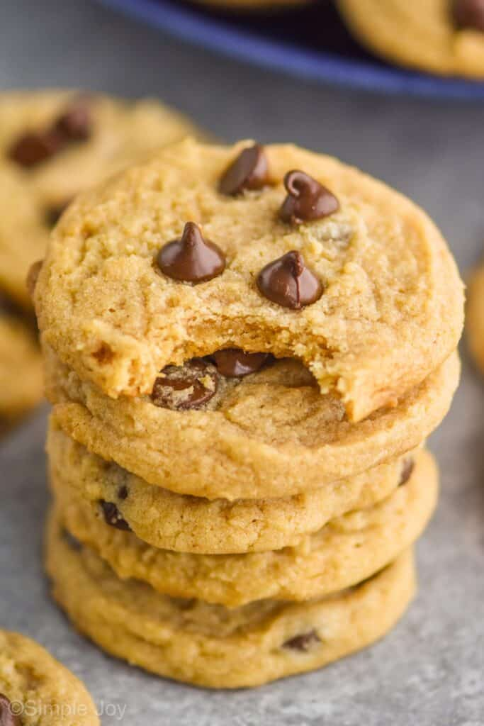 a stack of peanut butter chocolate chip cookies with the top one missing a bite