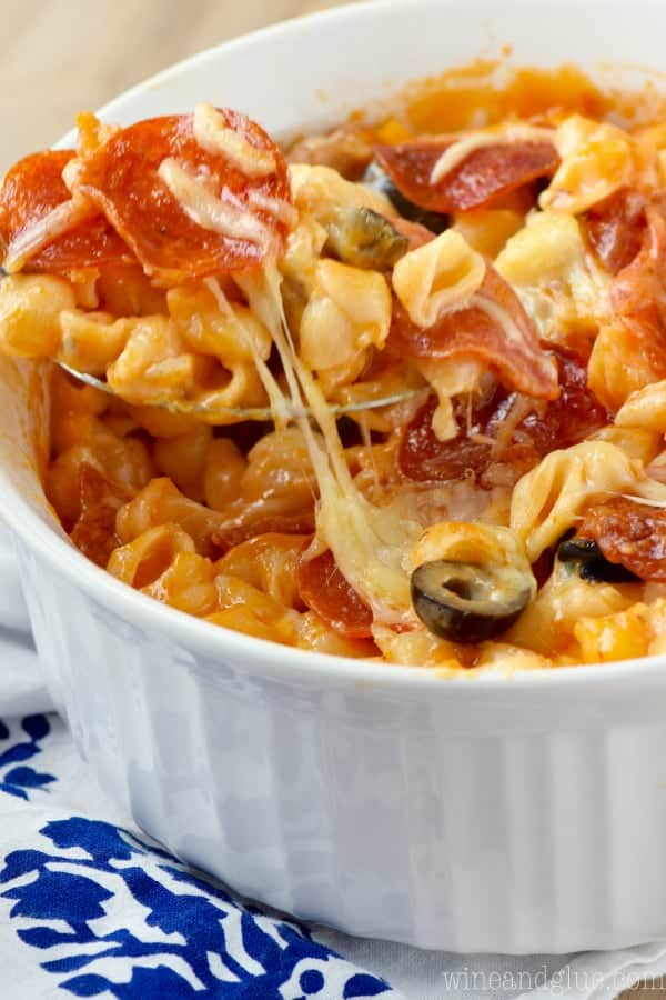 In a small bowl, the Pizza Mac N. Cheese has sliced pepperoni, sausage, and olives in a cheesy sauce.