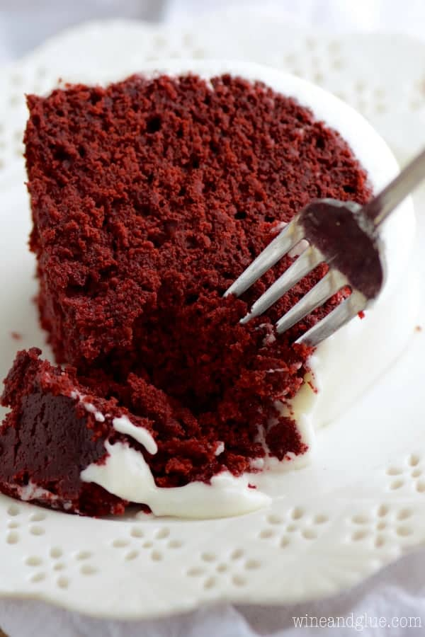 A fork digging into a the moist and airy Red Velvet Bundt Cake with a Cream Cheese Buttermilk Frosting drizzled on the side.
