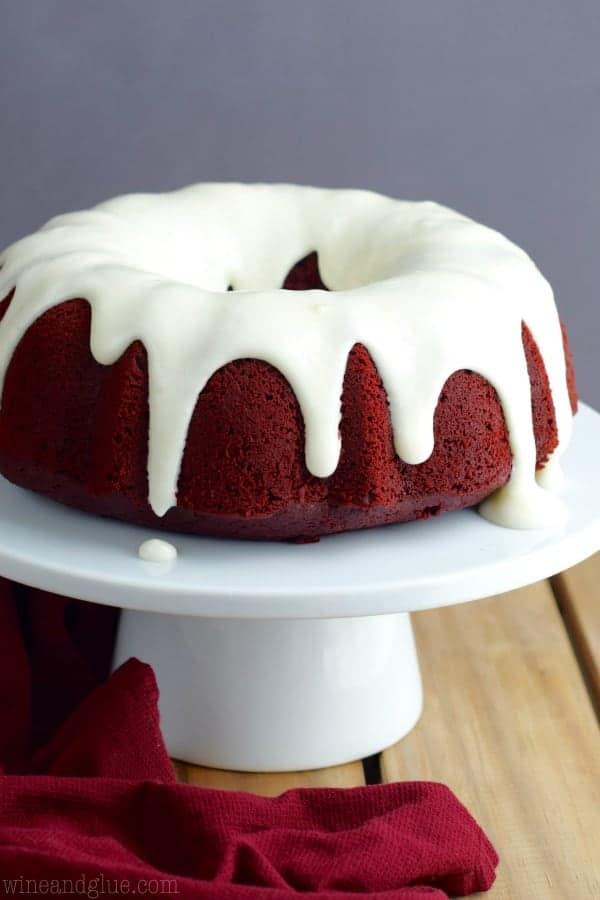 On a cake stand, the Red Velvet Sour Cream Bundt cake has a beautiful dark red cake layer and dripping from the sides is the Cream Cheese Buttermilk Frosting.