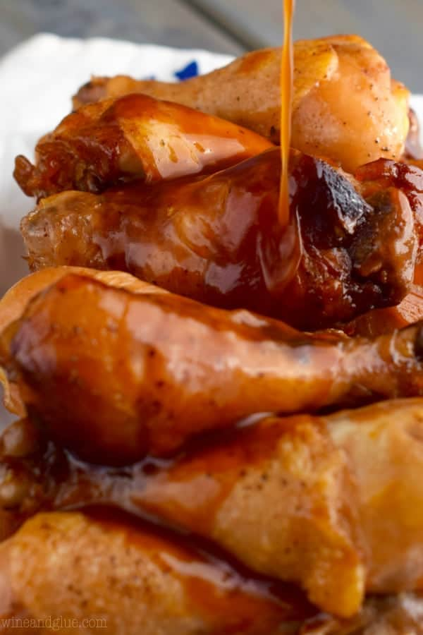 The crispy Slow Cooker Honey BBQ Chicken Drumsticks are being glazed with a golden Honey BBQ sauce.