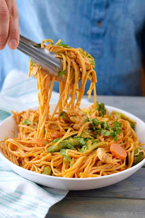 In a bowl, the Sriracha Noodles are being picked up with a pair of metal tongs.