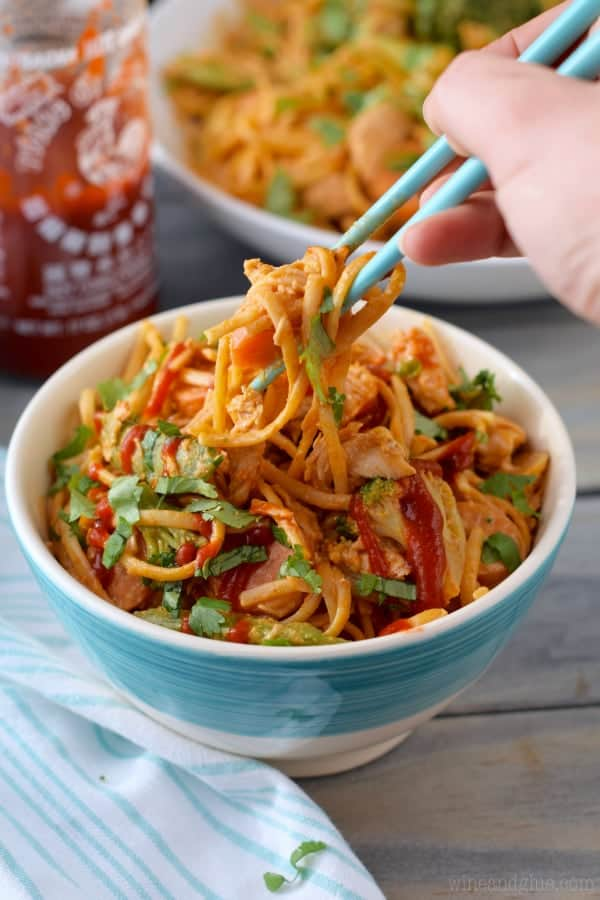 A pair of blue chopsticks is picking up some of the Sriracha Noddles from a blue bowl.