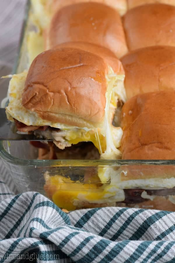 In glass casserole dish, a single Breakfast Slider is being picked up with a spatula showing the oozing egg yolk and cheese.