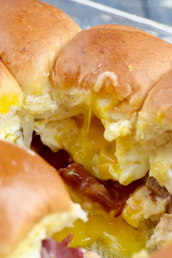 In a glass casserole dish, a single slider has been taken out showing the oozing egg yolk and melted cheese on top of the egg, turkey bacon, and turkey sausage.