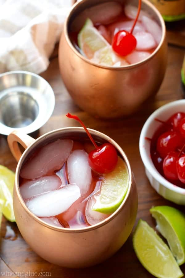 In copper mugs, the Cherry Moscow Mules has cubed ice, red tint, a maraschino cherry, and a sliced lime.