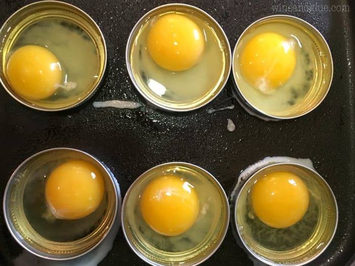 An overhead photo of eggs cracked into mason jar lids on a hot skillet.