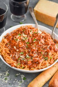 a large white serving bowl full of chicken spaghetti - a spaghetti with red sauce and shredded chicken garnished with parsley and fresh parmesan