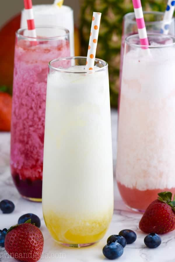 In long glasses, the Skinny Italian sodas have different flavorings of blueberry, strawberry, and lemon with some cream placed into it.