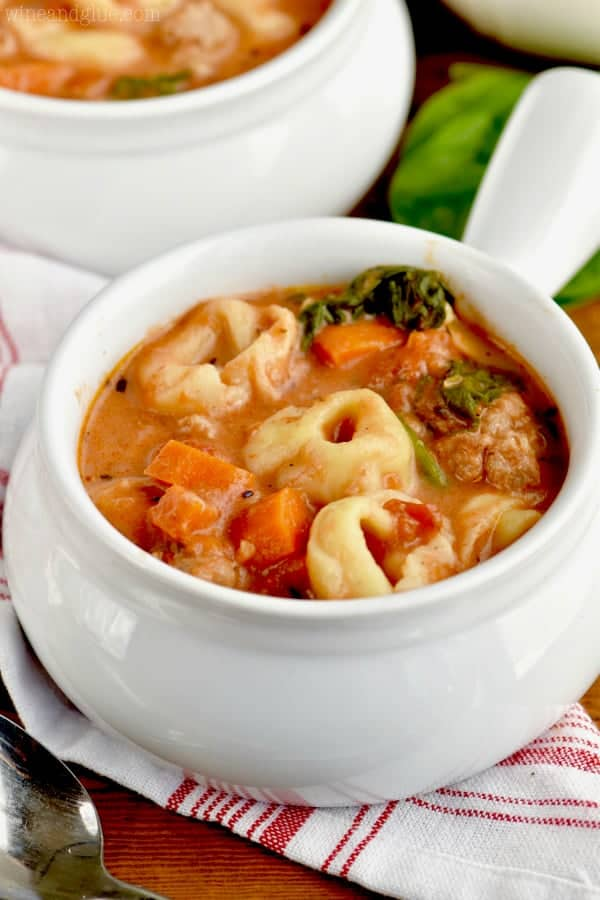 In a small white bowl, the Slow Cooker Creamy Tortellini Soup has spinach, sausage, and chunks of carrots in a creamy tomato soup.