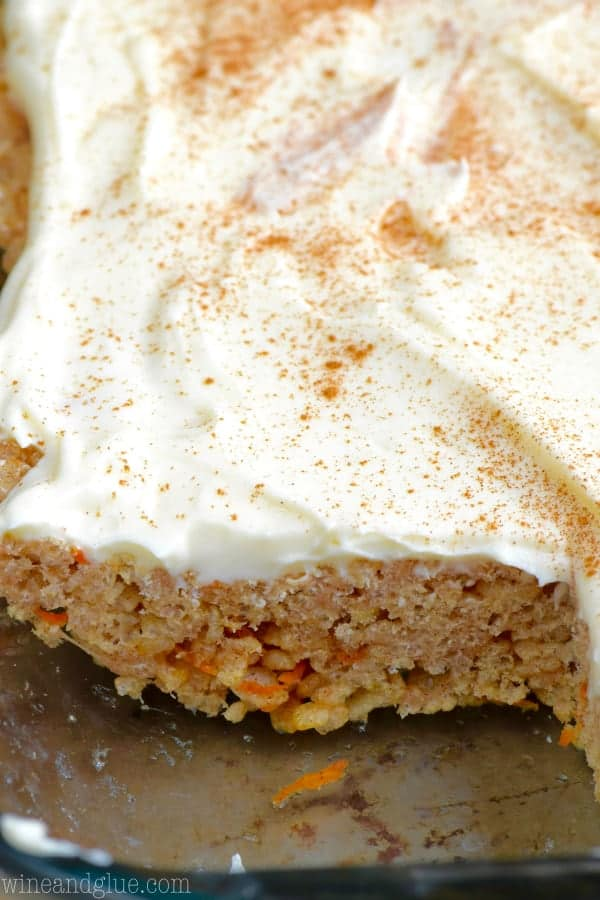 In a a glass casserole dish, the Carrot Cake Rice Krispies has a small slice that was cut out showing the little shreds of carrot that is mixed in with the rice krispies.