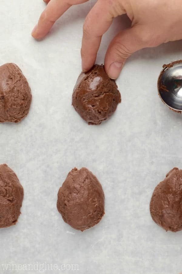 A woman is pinching the top of the fudge ball to create an egg shape.