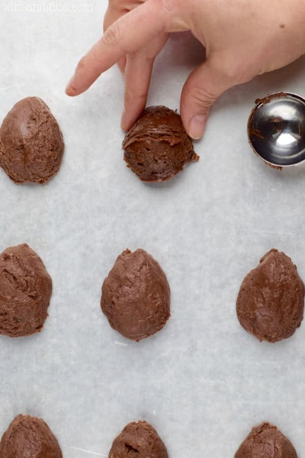 A woman pinches the top of the fudge ball to create an egg shape.
