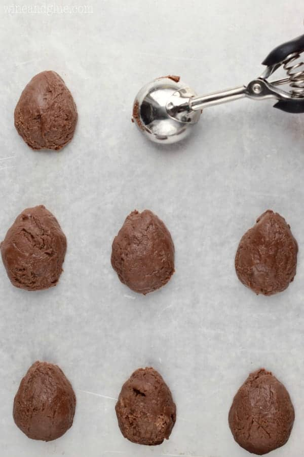 The creamy chocolate fudge is being scooped on a parchment paper with the ice cream scooper then being shaped into little eggs.