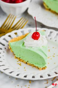 piece of green shamrock shake pie on a white plate topped with whipped cream and a cherry