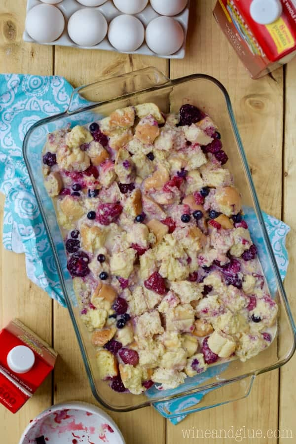 In the glass casserole dish, the pre-cooked Overnight Berry Cobbler French Toast is ready to be cooked.