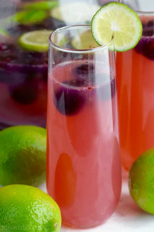 The Cherry Limeade Sangria has a pink red tint has some black cherries floating in the drink with a slice lime on the rim.