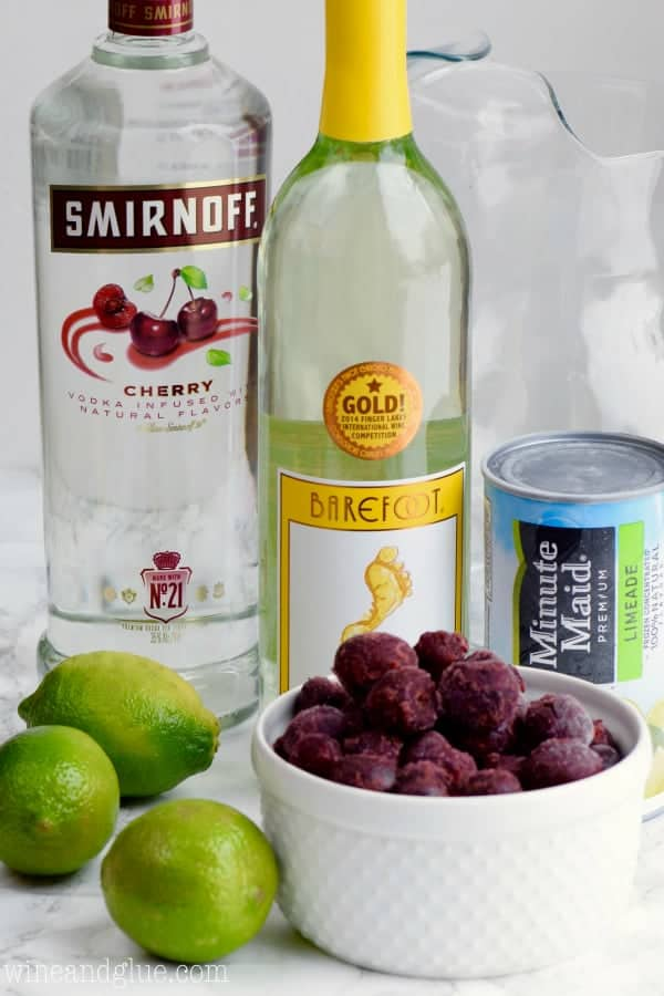 A picture of the ingredients of the Cherry Limeade Sangria (Limes, Minute Maid's Limeade, White Wine, Smirnoff's Cherry vodka, and frozen cherries).