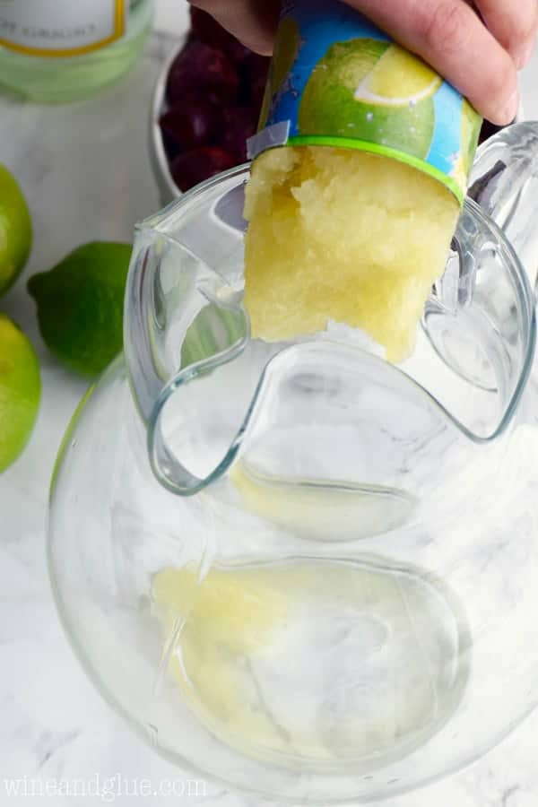 Frozen Limeade is being poured into a large pitcher.