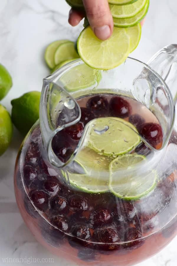 Slices of lime are being placed into the pitcher.