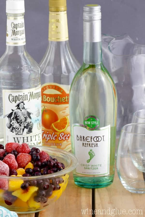 A picture of the ingredients for the Frozen Fruit sangria (white wine, white, rum, orange liquor, and frozen fruit).