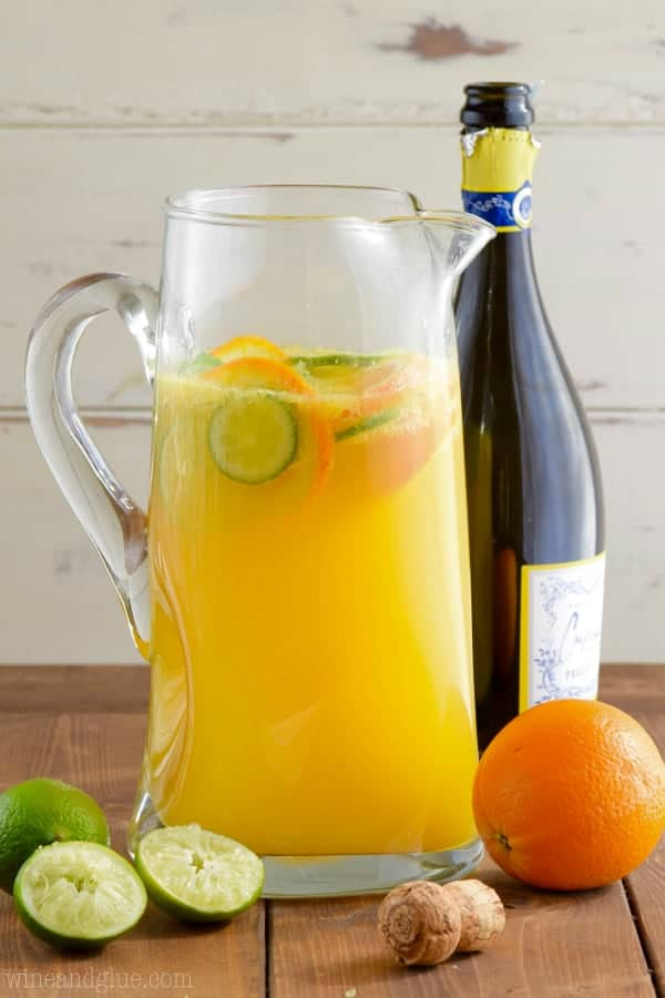 In a large pitcher, slices of limes and oranges float in an orange liquid called the Mimosa Margaritas.