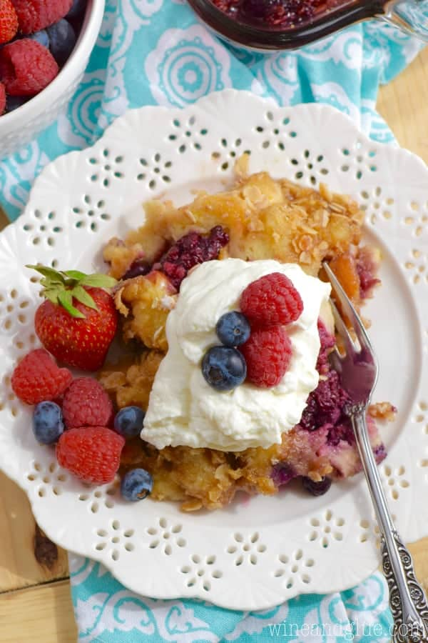 An overhead photo of the Overnight Berry Cobbler French Toast on a white plate and topped with homemade whipped cream and berries.