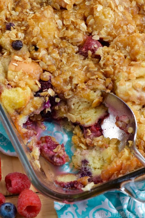 In a glass casserole dish, the Overnight Berry Cobbler French Toast is topped with oats and berries are sprinkled throughout the cobbler.