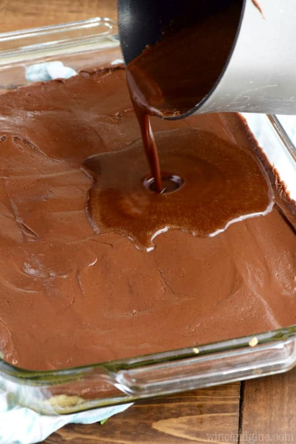 Chocolate is being poured onto the fudge layer in the Sugar Cookie Fudge Bars.