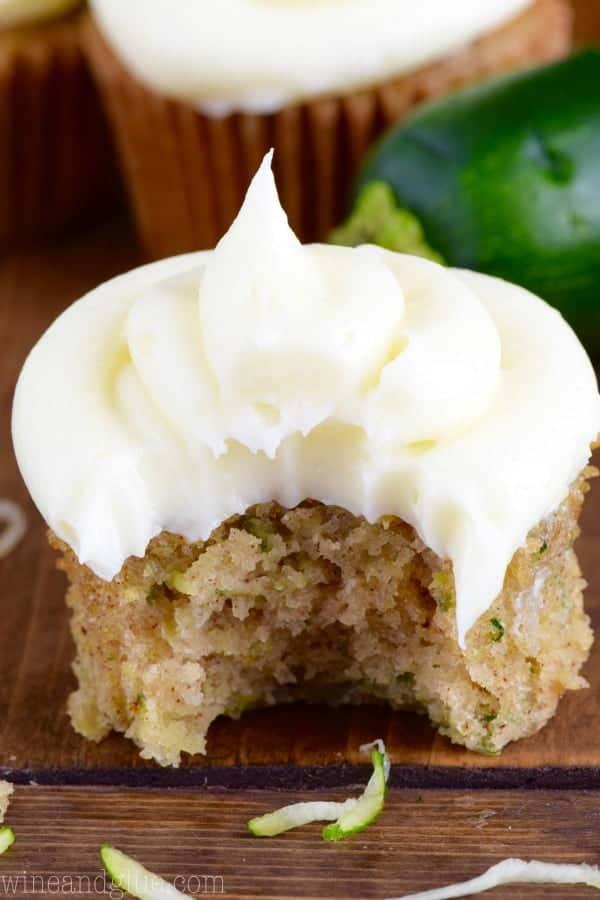 In a cupcake tin, the Zucchini Cupcake has a large bite in it showing the a dark golden brown color and topped with a fluffy cream cheese frosting.