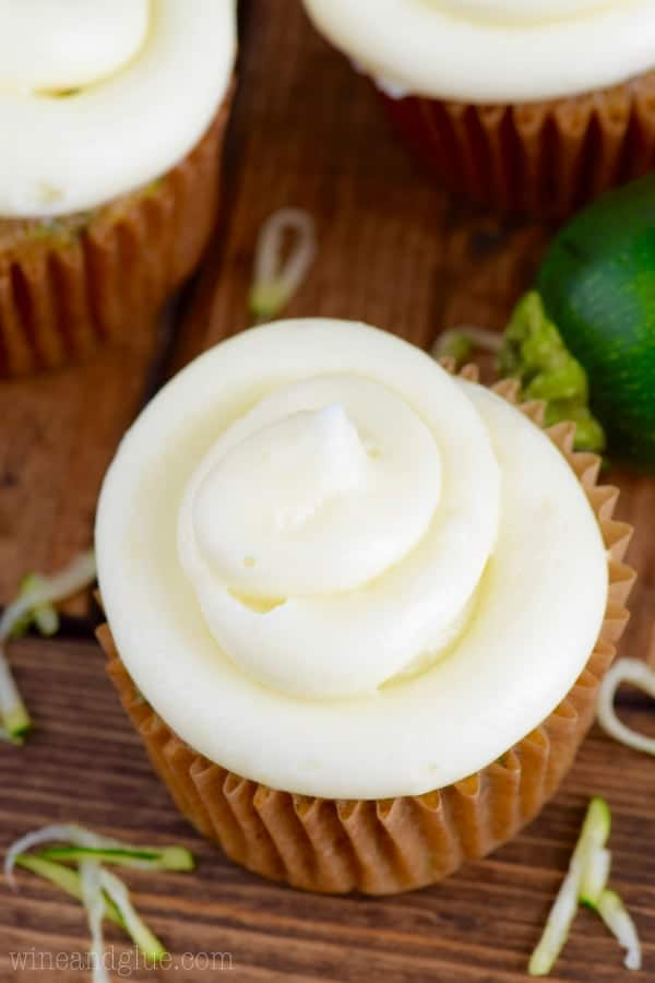 In a cupcake tin, the Zucchini Cupcake has a dark golden brown color topped with a fluffy cream cheese frosting.