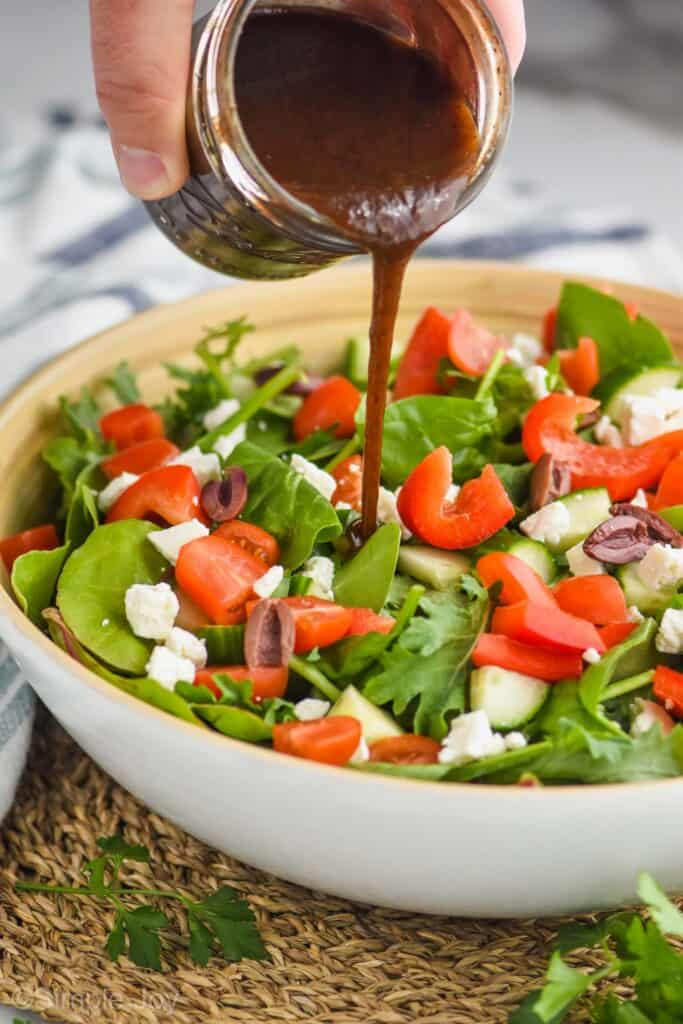 a hand pouring balsamic salad dressing onto a salad with mixed greens, tomatoes, red peppers, feta cheese, and kalamata olives