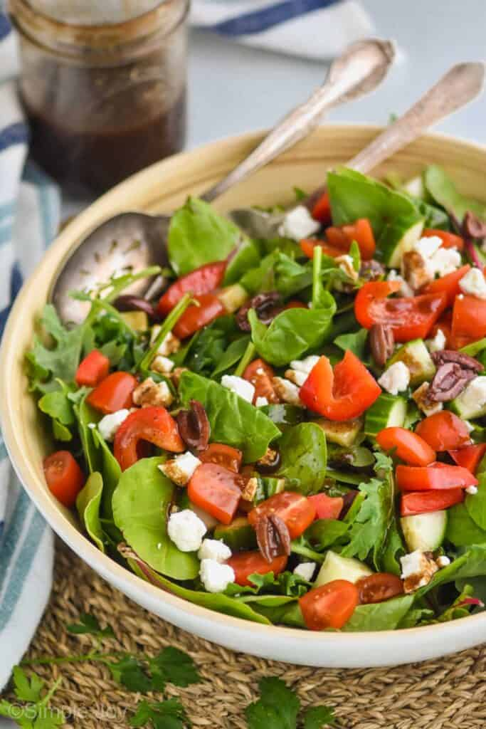 a mixed green salad with red peppers, feta cheese, kalamata olives, and tomatoes tossed with balsamic vinaigrette dressing
