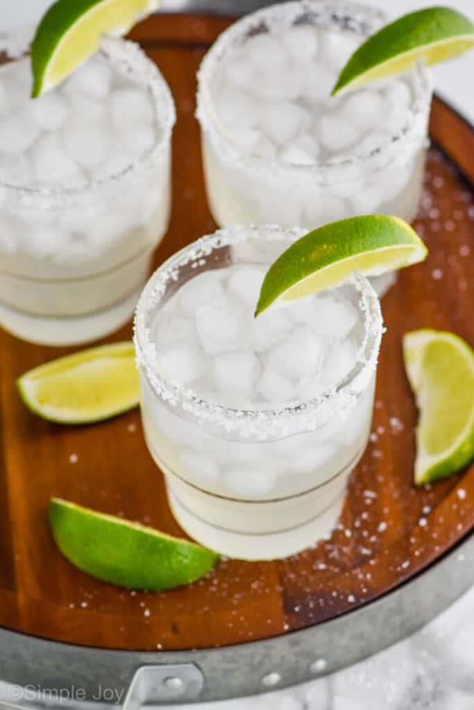 overhead view of three tumblers with margarita recipe in them, ice, salted rims, lime wedges on a wooden tray that has salt around it and three lime wedges