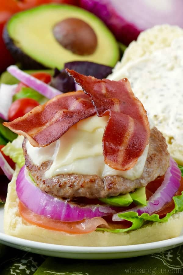 Without top bun, the California Club Burger has turkey bacon, turkey patty, melted cheese, red onion, tomatoes, and lettuce.