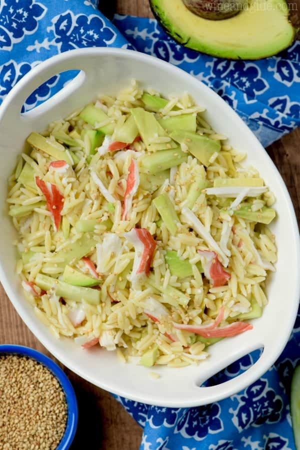 In a white bowl, slices of avocado and crab meat has been mixed within the Orzo Pasta and topped with white sesame seeds.