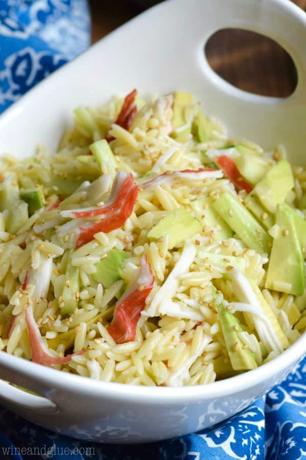White bowl filled with orzo pasta salad recipe topped with white sesame seeds.