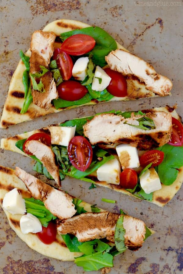 Three pieces of Grilled Capese Flat Bread topped topped with basil, grilled chicken, cherry tomatoes, and mozzarella.