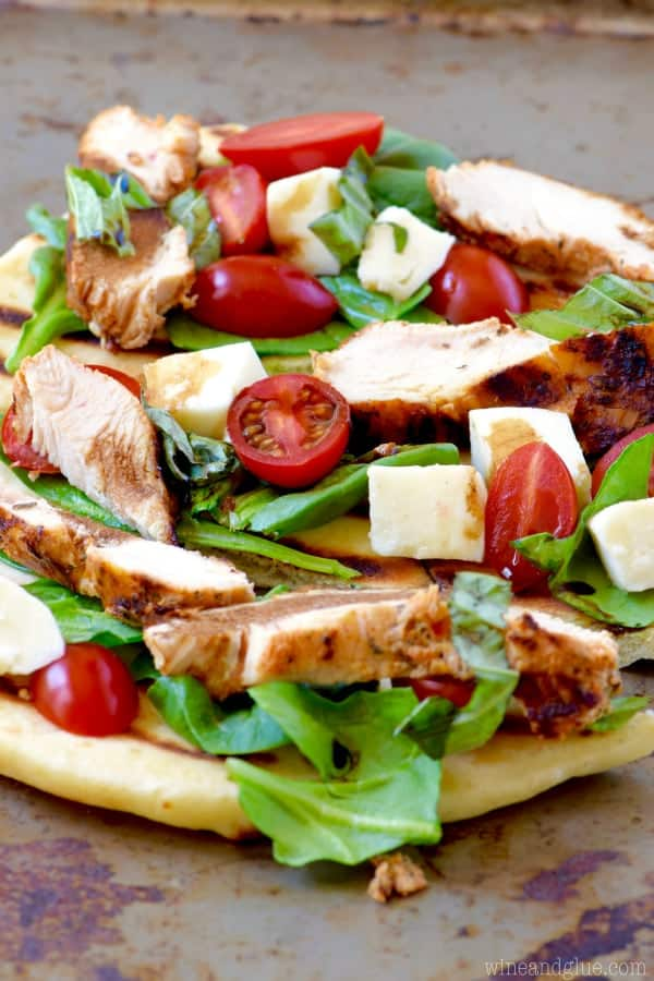 On a baking sheet, the Grilled Chicken Capese Flatbread has sliced cherry tomatoes, basil, grilled cheese, and mozzarella.