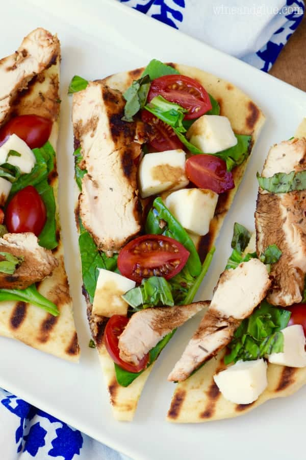 An overhead photo, three Grilled Chicken Capese Flatbread showing the grilled chicken, halved cherry tomatoes, cheese, and basil.