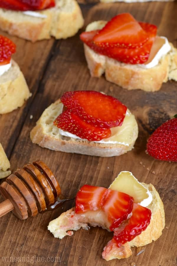 On a slice of baguette, a slice of Brie is topped with two thin slices of strawberry and honey is drizzled on top to make the Honey, Strawberry, and Brie Bruschetta.