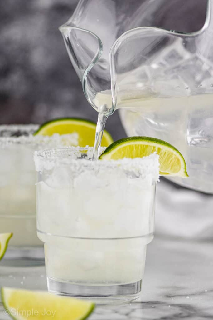 a glass pitcher pouring the best margarita recipe into a glass filled with ice with a salted rim and a lime wedge on the rim, another margarita blurred in the background