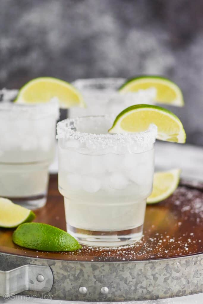 three small tumblers filled with a margarita recipe with salted rims and lime wedges on a wooden tray that has a galvanized metal rim with three lime wedges and lots of spilled kosher salt on the tray
