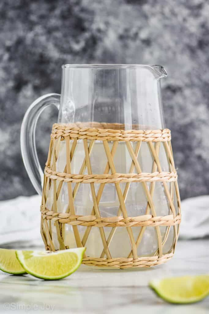 glass pitcher with a straw outside holder that has homemade margaritas in it