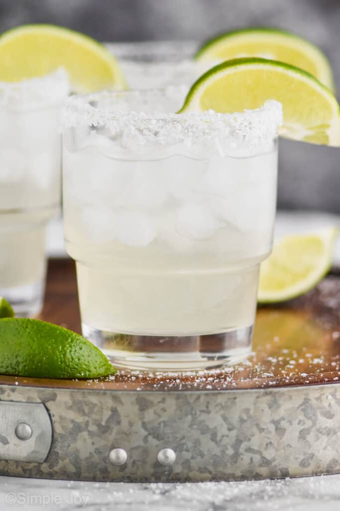 up close straight on view of a tumbler full of a margarita on ice with a salted rim and a lime wedge, two blurred margaritas int he background on a galvanized metal and wooden tray