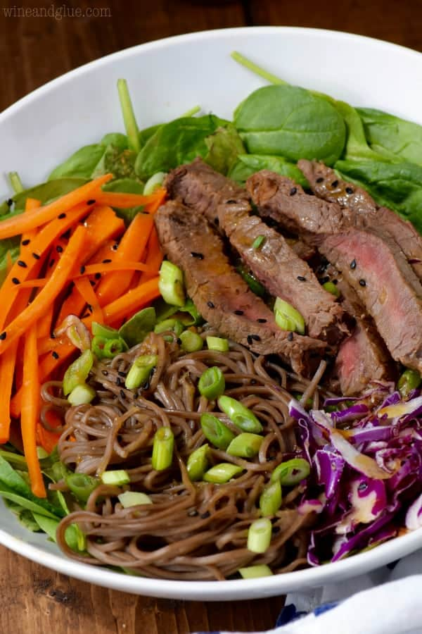 An overhead photo of a bowl of the Soba Noodle Steak Salad that has spinach, carrots, sliced steaks, red cabbage, soba noddles, and topped with black sesame seeds and scallions.