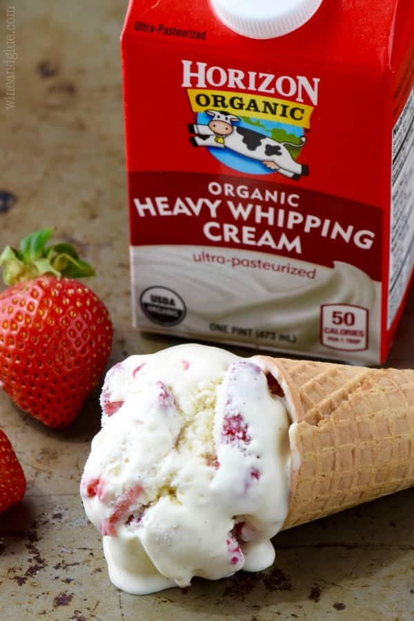A scoop of Strawberry and Cream Ice Cream in a waffle cone in front of Horizon Organic Heavy Whipping Cream.