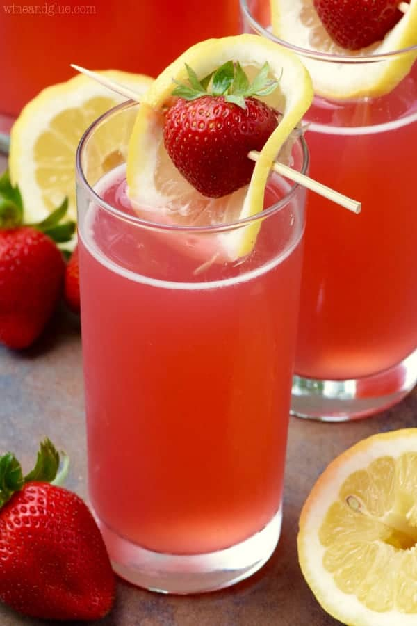 The Strawberry Lemonade Beergaritas is in in a tall glass and topped with a sliced lemon covering a strawberry in a toothpick.
