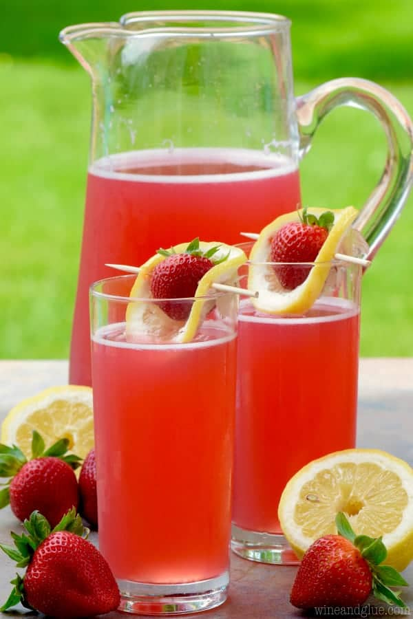 Two glasses of the Strawberry Lemonade Beergaritas are in front of a pitcher of the drink which has a pink red tint.