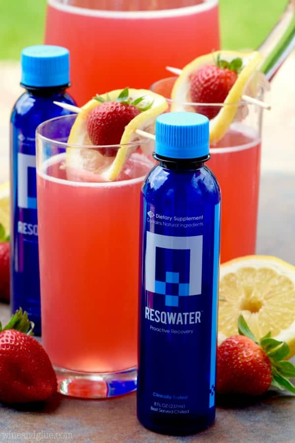The glass of Strawberry Lemonade Beergaritas are in between two bottles of Resqwater.